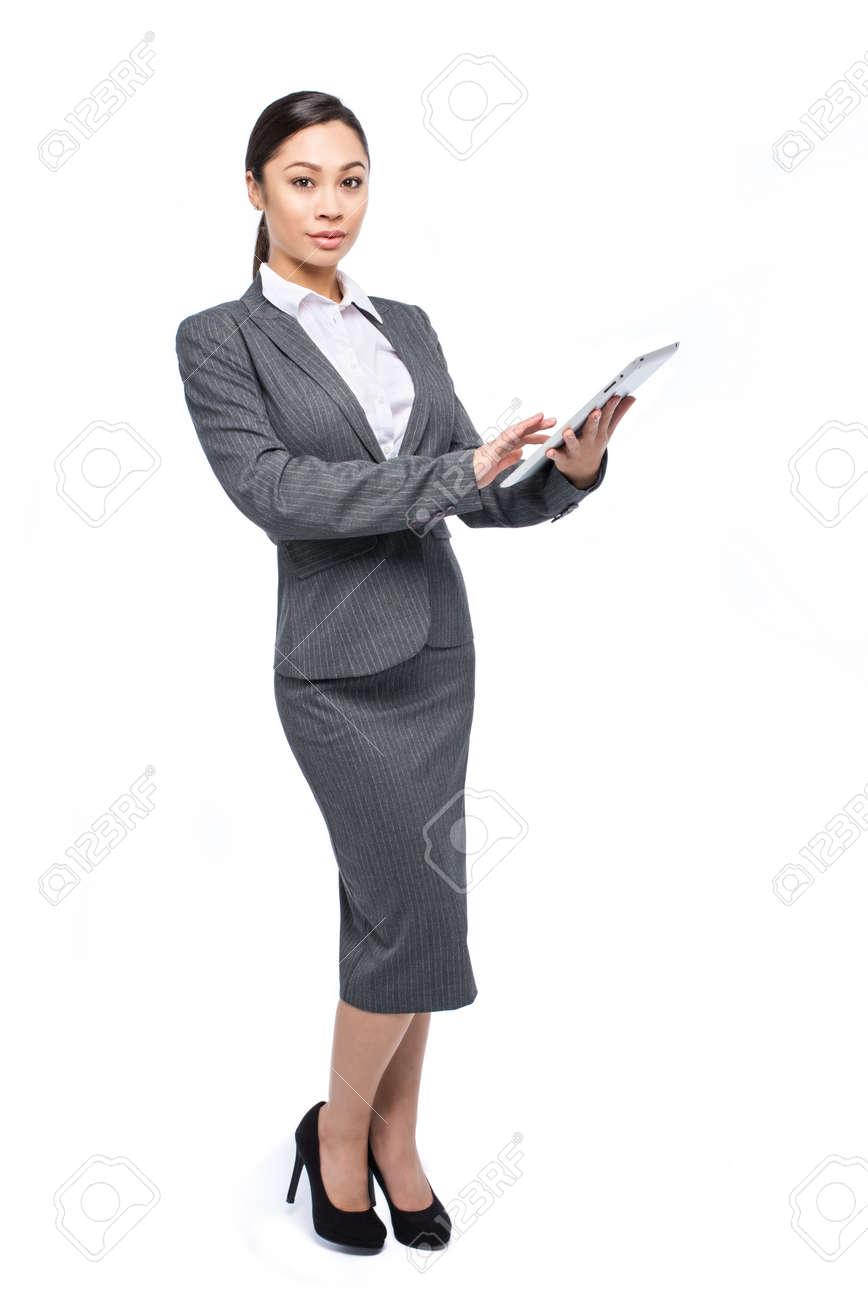1af2312ab Foto de archivo - Mujer asiática ejecutivo inteligente con una tableta ipad  vestido con un traje gris y un disparo en el estudio sobre un fondo blanco.