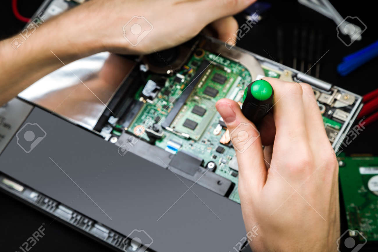 Repair a broken laptop with details and special tools on a black