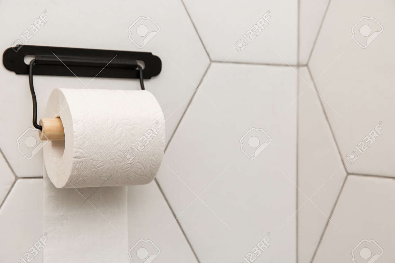 A White Roll Of Soft Toilet Paper Neatly Hanging On A Modern Stock