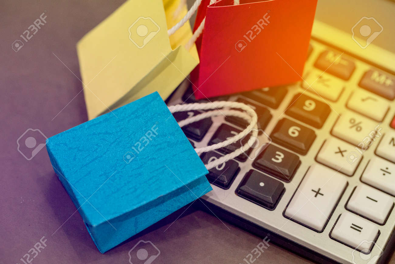 closeup shot of blue color paper shopping bags on a calculator