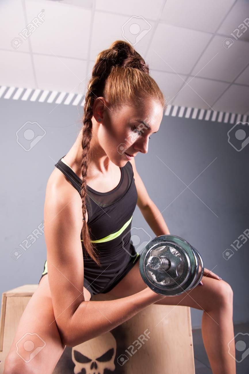 Banque d images - Jeune femme confiante faire biceps exercice boucle avec  des haltères dans le centre de remise en forme. la formation de fille Slim  dans le ... 981d8d4d31d