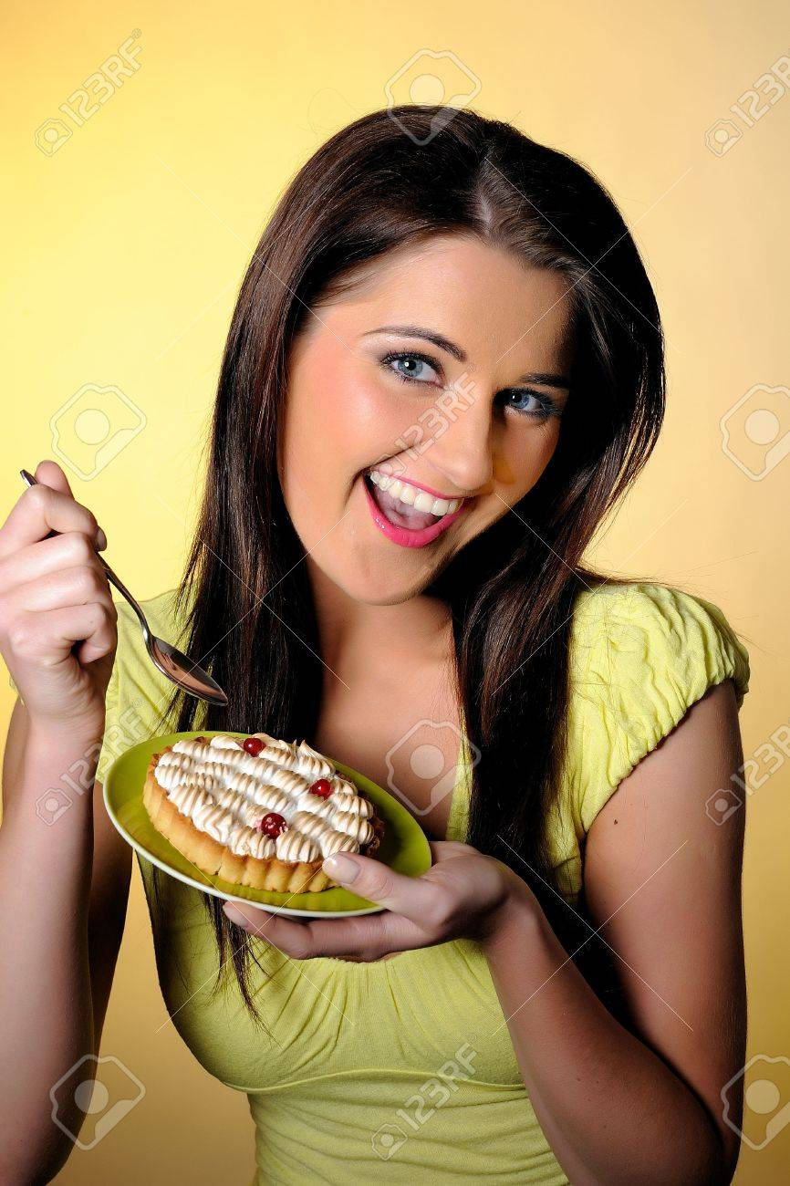 young beautiful girl eating small sweet cake. yellow background Stock Photo - 6868494