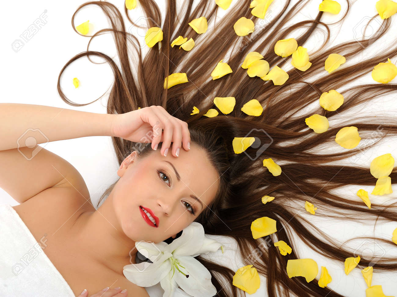 Beautiful spa woman with long healthy hair and bright make-up relaxing on the floor with yellow rose petals. isolated on white background Stock Photo - 8365647