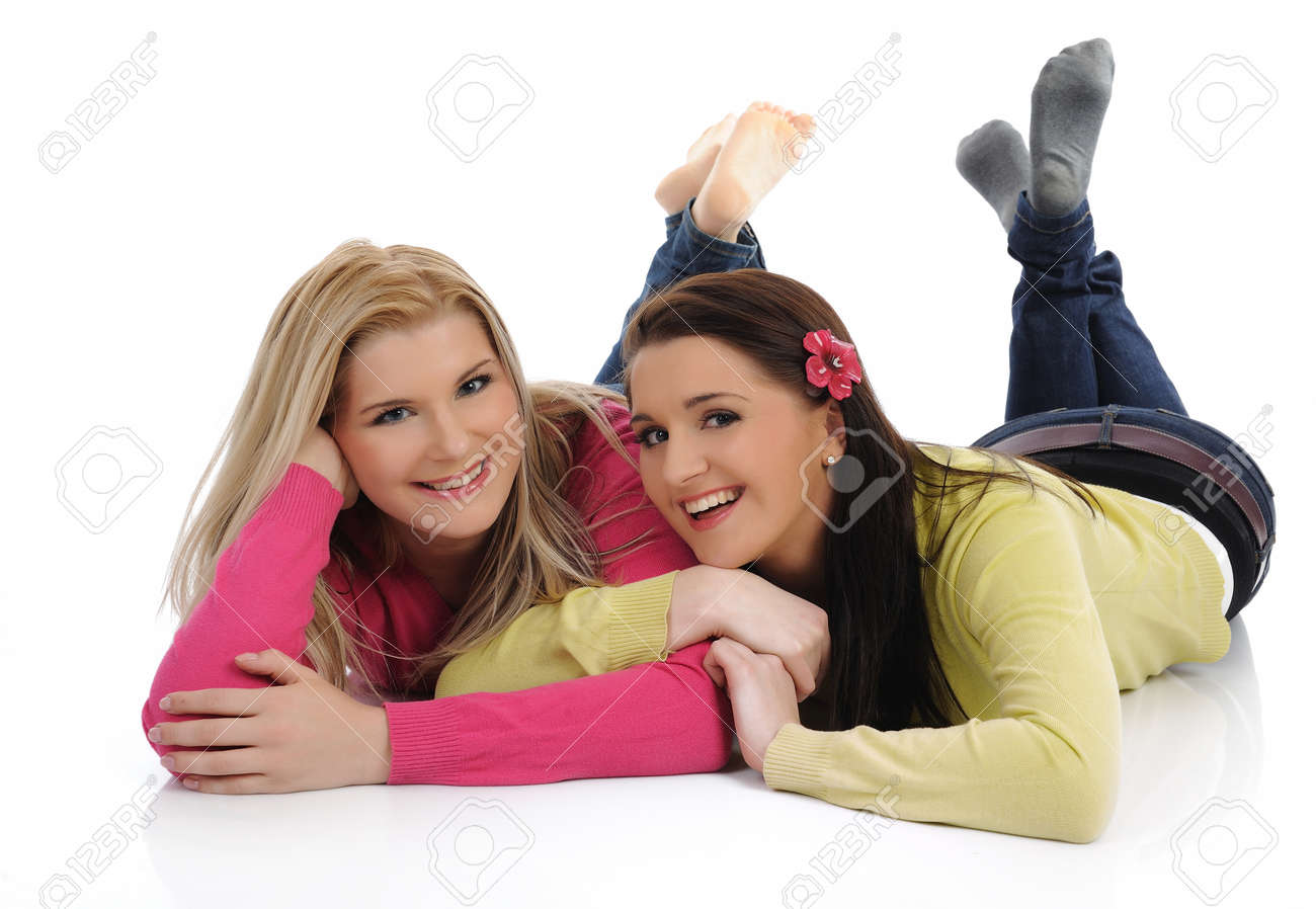 Two pretty girl friends having fun and laughing on the floor. isolated on white background Stock Photo - 8400189