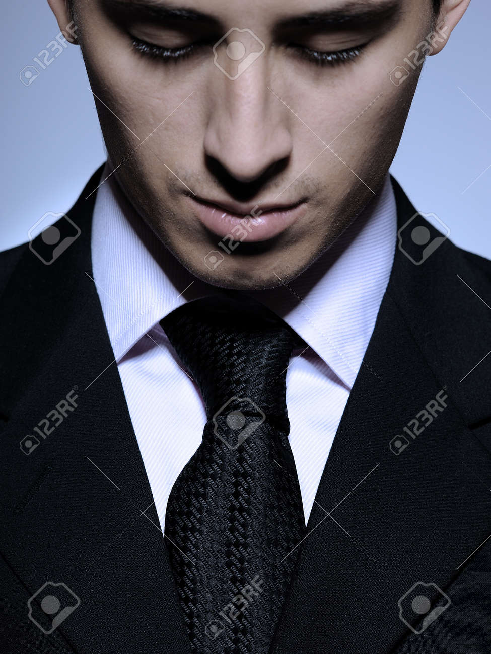 Portrait of succesful  business man in formal suit and black tie looking down. gray background Stock Photo - 8598689
