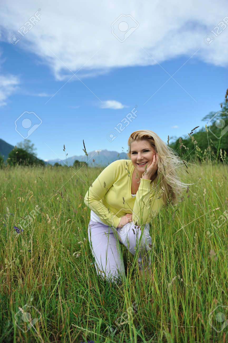 Pretty healthy summer woman outdoors on green field in Alps enjoying freedom. Switzerland Stock Photo - 9678405