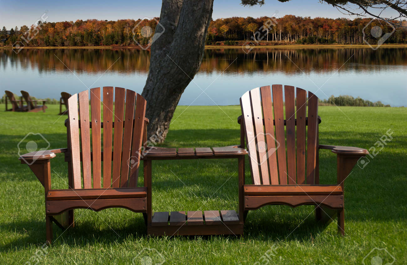 Muskoka - Adirondack chairs in front on still lake with fall colours in the background Stock Photo - 18092632