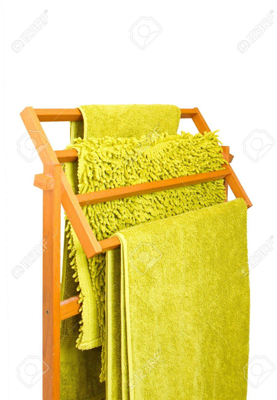 Green towels hanging on a wooden towel rail isolated Stock Photo - 16803340