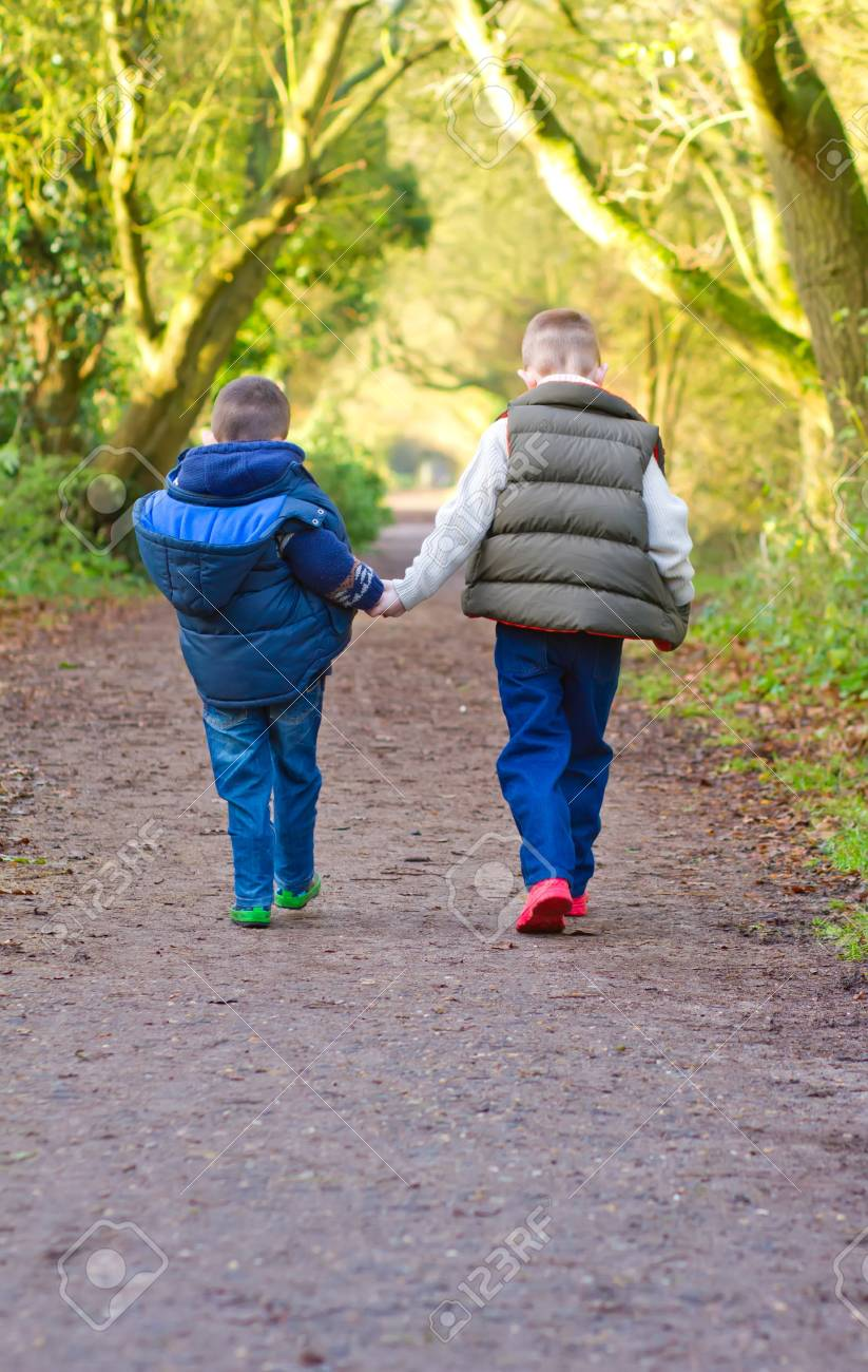 brothers holding hands on a countryside path Stock Photo - 17277101