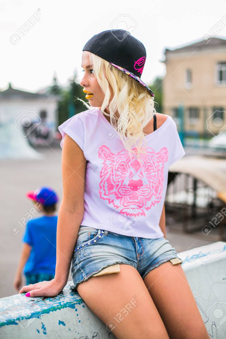 Portrait of a young blond swag girl in cap outdoors.