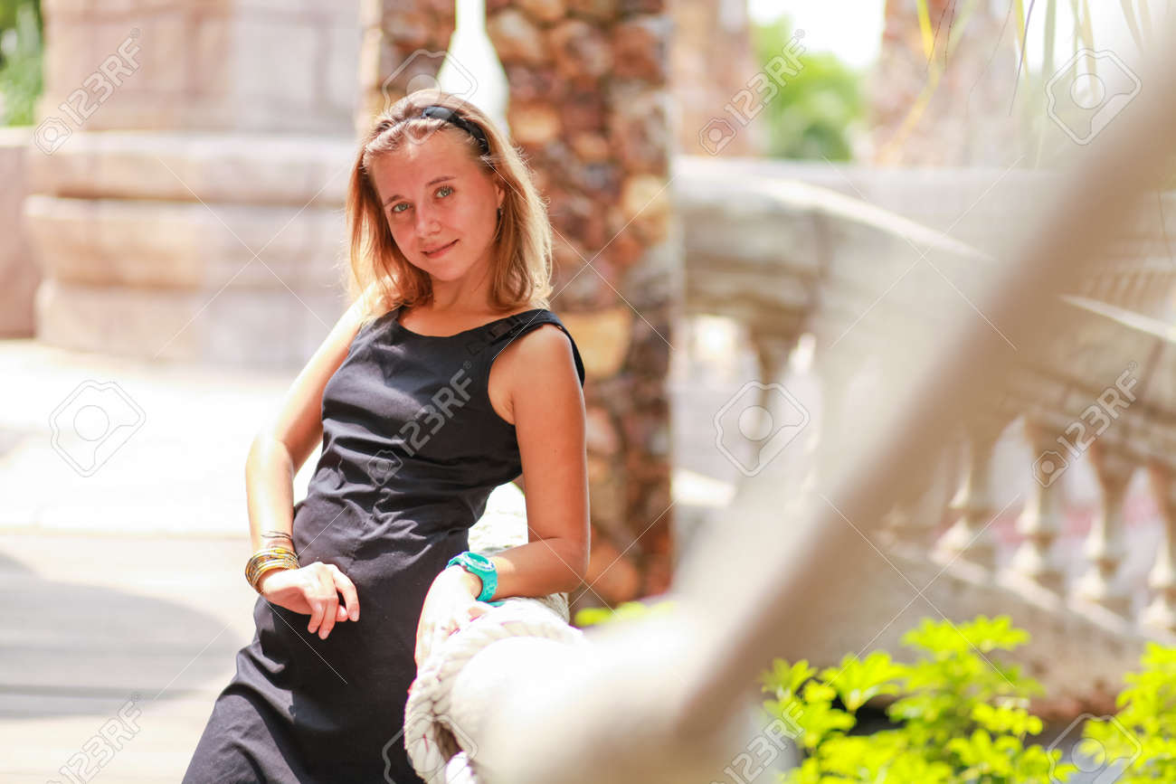 14be3185002 Outdoor summer portrait of young beautiful girl with blond hair posing in short  black stylish dress