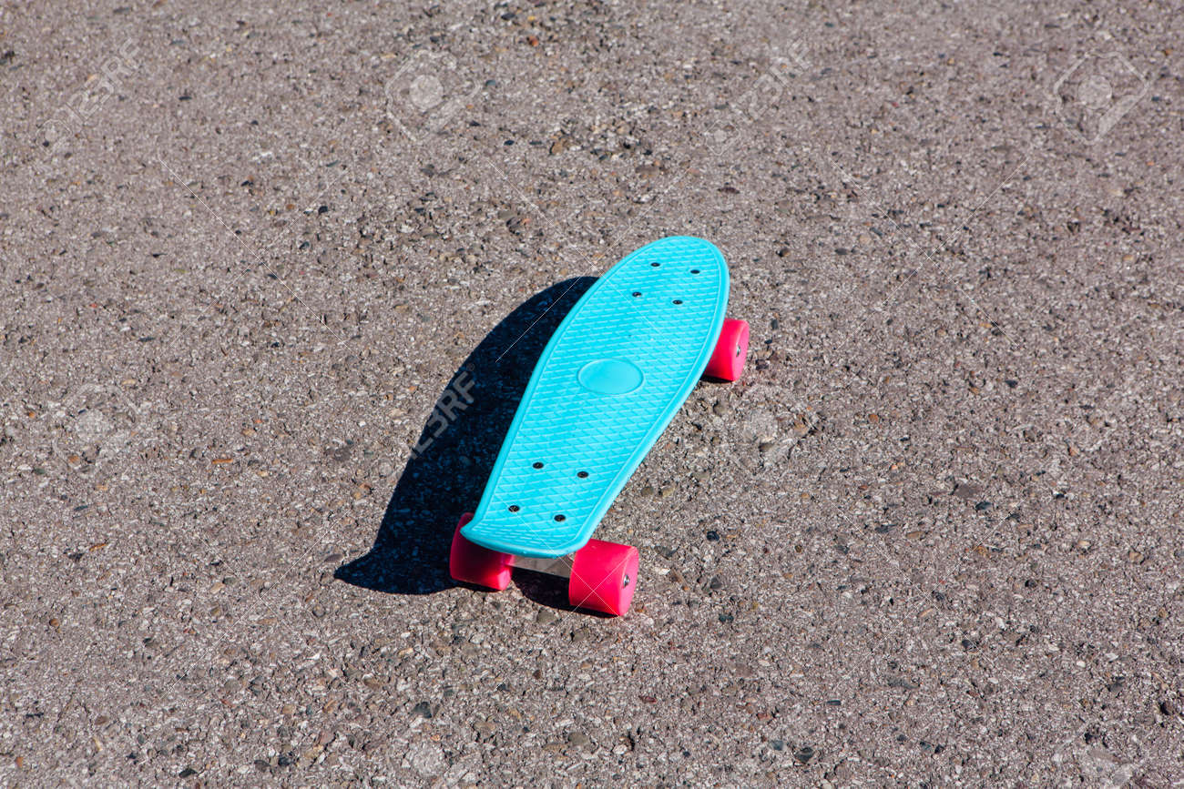 486e4961e8 Blue plastic skateboard penny board with pink wheels stands on the track.  Stock Photo -