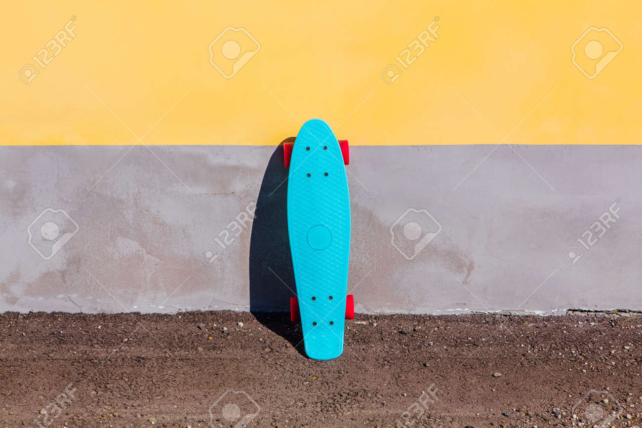 444d8848a8 Blue plastic skateboard penny board with pink wheels stands next to the  wall. Stock Photo