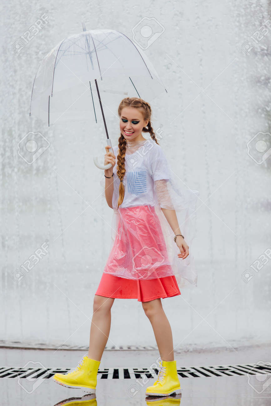 Young pretty girl with two braids in yellow boots and with transparent umbrella stands near fountain. Rainy day in city. - 122510632