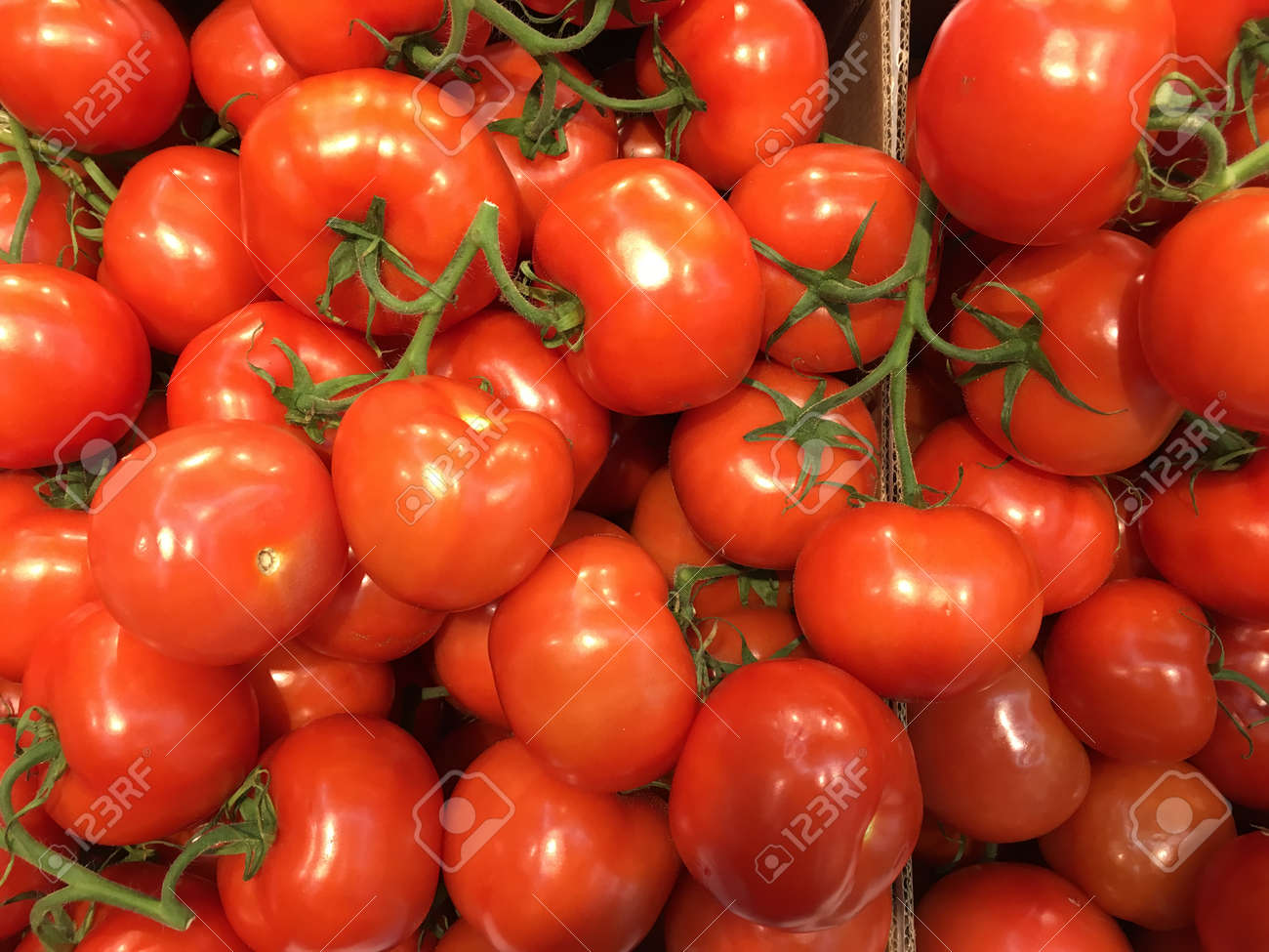 Tasty red tomatoes with green leaves in the box on market - 122517177