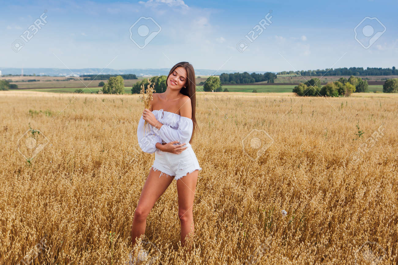 Rural Countryside Scene. Young beautiful woman with long hair dressed in white relaxing at golden oat field. Summer landscape with blue sky - 157216076