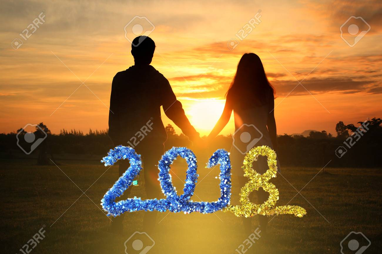 happy new year 2018 shadow image of couples holding hands with the morning light