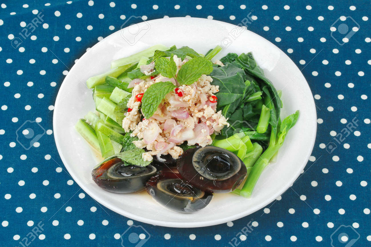 Spicy cucumber salad with Chinese kale and preserved egg topped