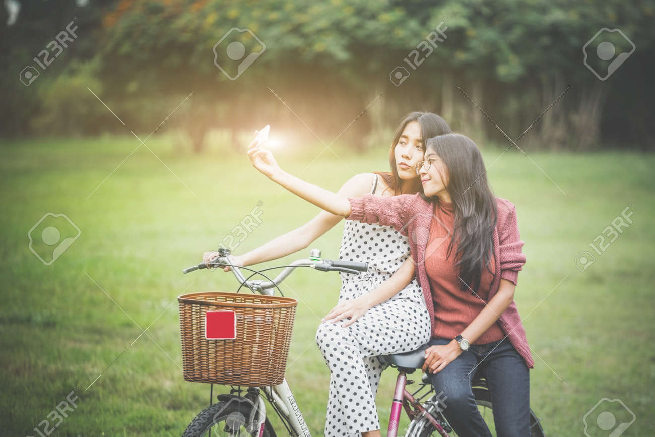Girls ride a bicycle in park, having fun by play together - 120464578