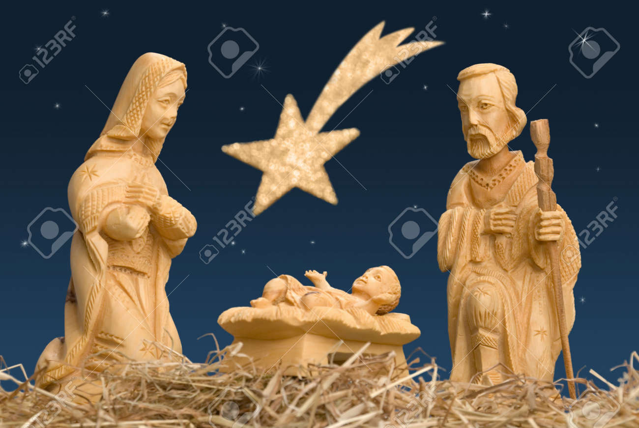 Wooden figures of Mary and Joseph watching baby Jesus, with night sky and comet Stock Photo - 3999275