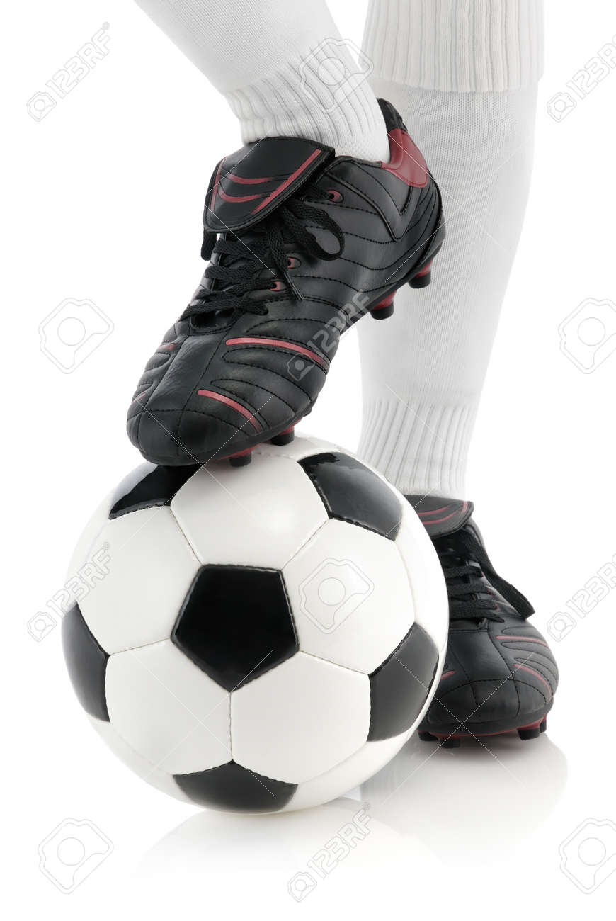 Football player with shiny black shoes keeps the ball under his foot, isolated studio shot Stock Photo - 13535613