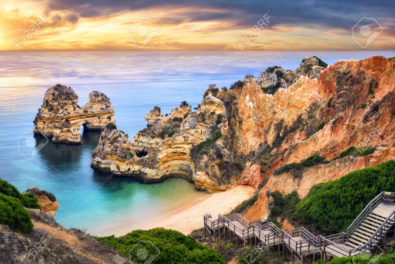 The beautiful Camilo Beach in Lagos, Portugal, with its magnificent cliffs and the blue ocean colorfully lit at sunrise - 44380196