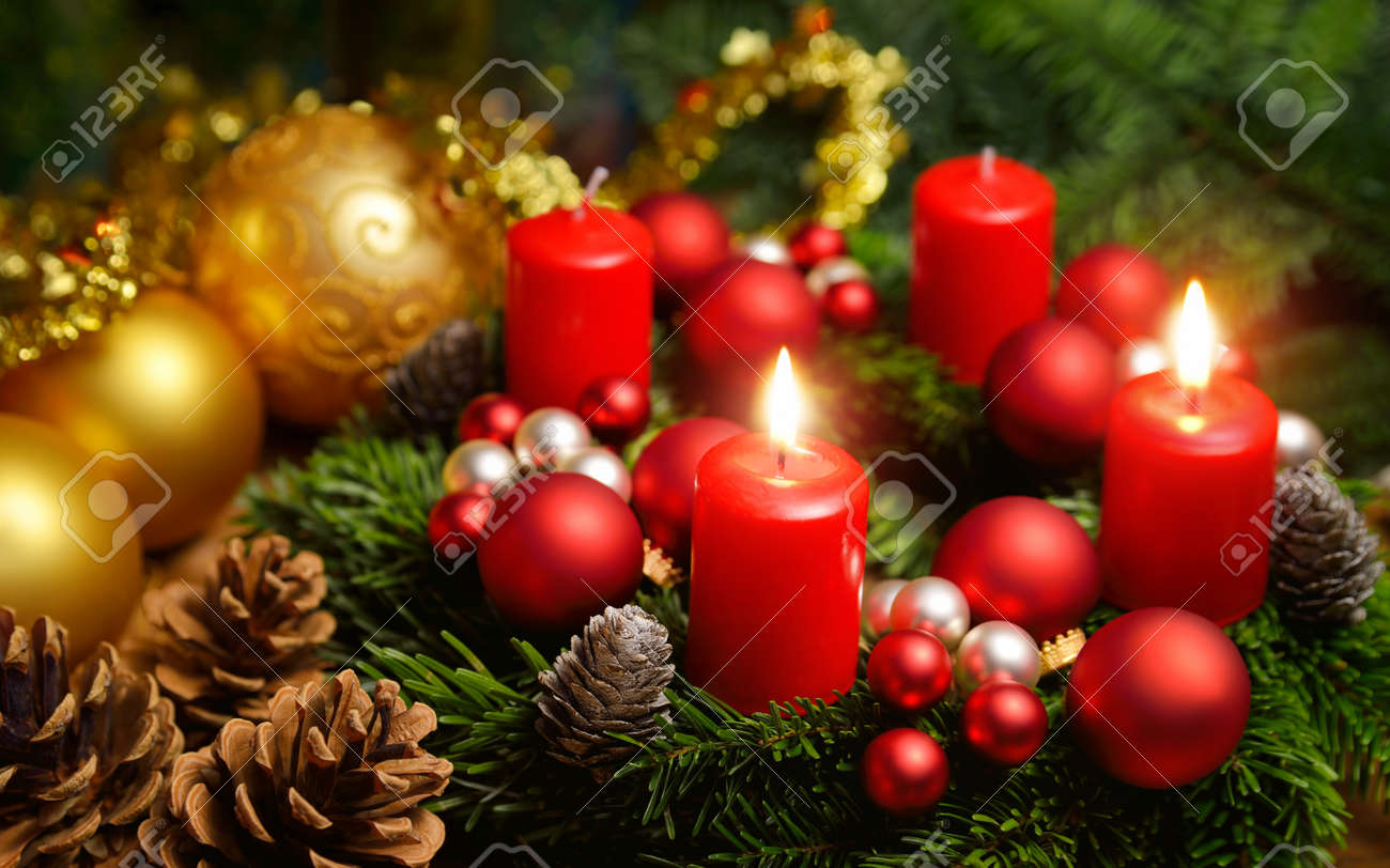 Studio shot of a nice advent wreath with baubles and two burning red candles - 47249366