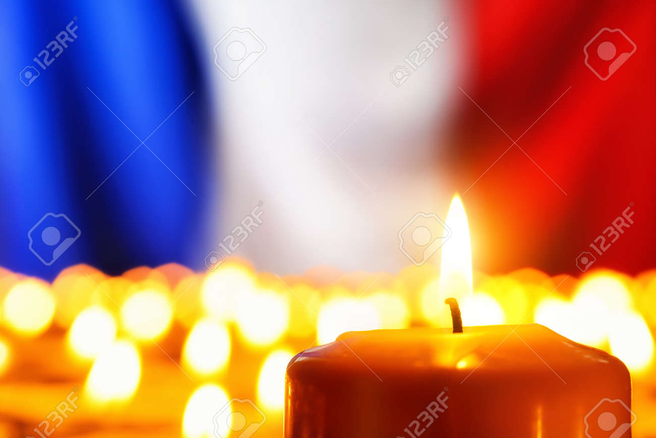 Lots of candles in front of the national colors of France in remembrance of the many victims of terror or to simply symbolize the great French spirit - 48548732