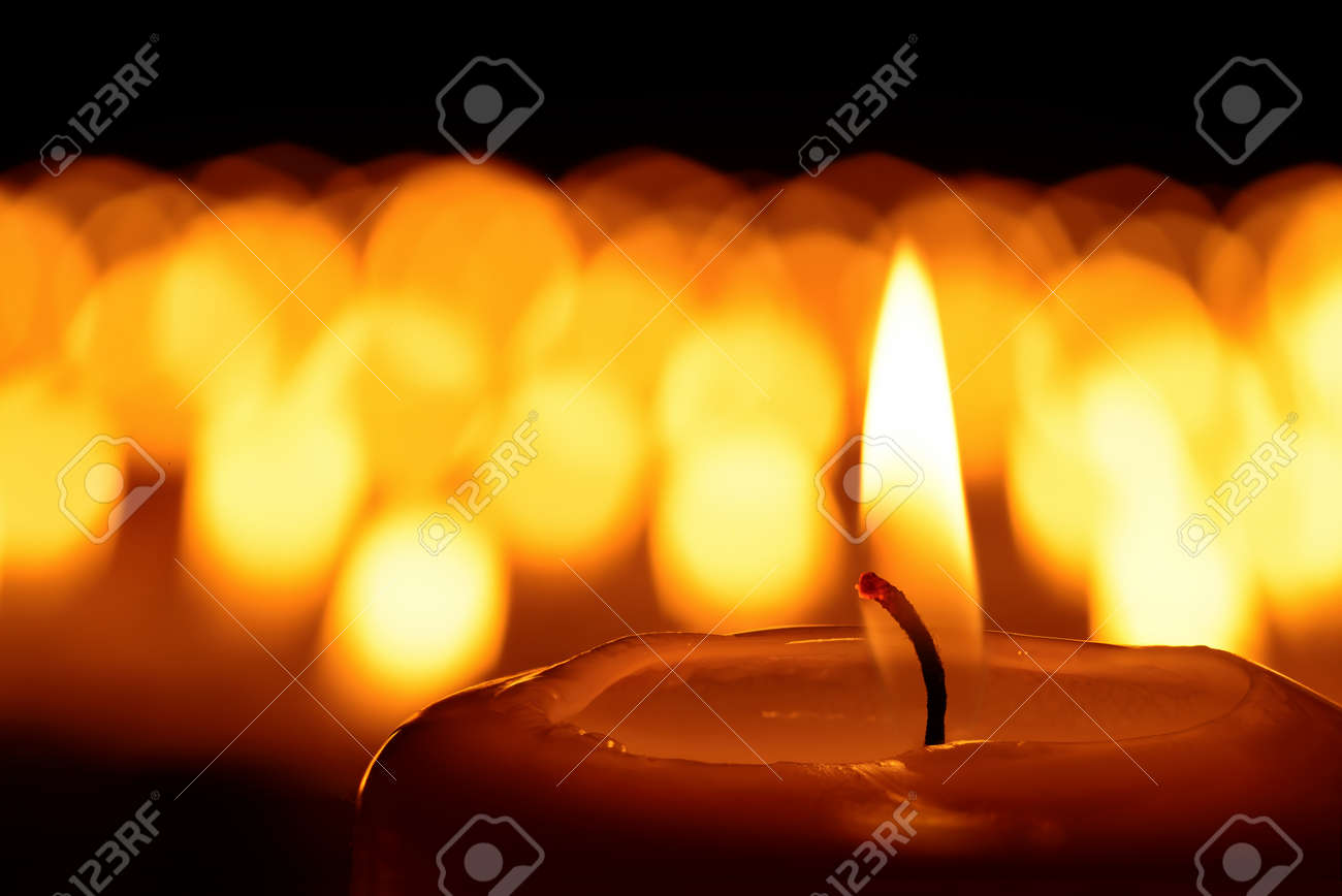 Candle in front of many defocused candleflames creating a spiritual atmosphere and in remembrance of loved ones - 48595530