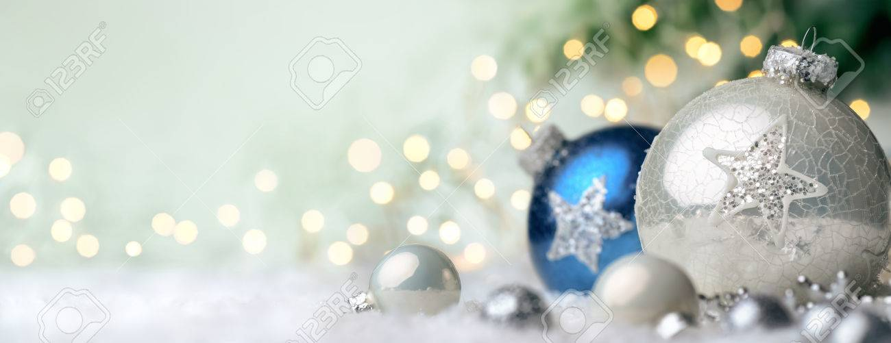 Panoramic Christmas background with nice shiny baubles on snow and defocused lights in the background, with light green copy space - 49188238