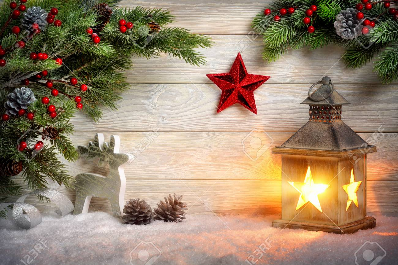 Christmas scene background with a lantern, fir branches, red star, reindeer and snow in front of a bright wooden board with candle light - 49188239