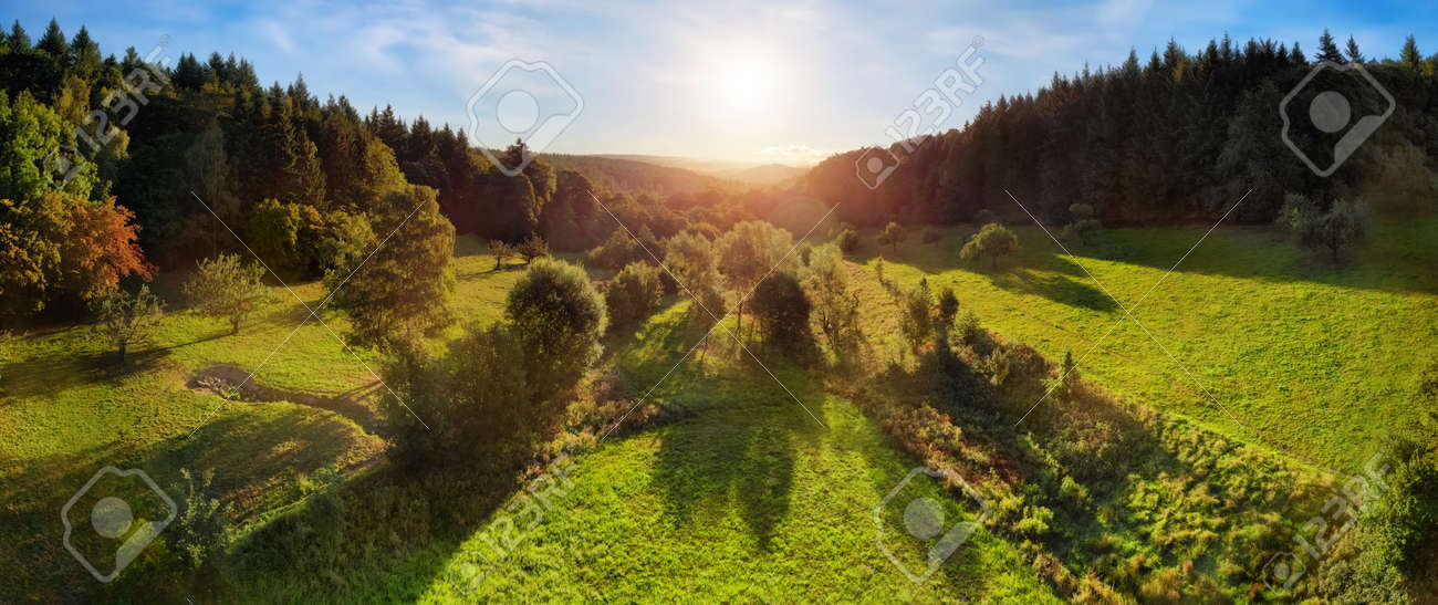 Aerial landscape panorama after sunrise: gorgeous scenery with the sun in the blue sky, trees on green meadows casting long shadows, surrounded by forests on hills - 146425349