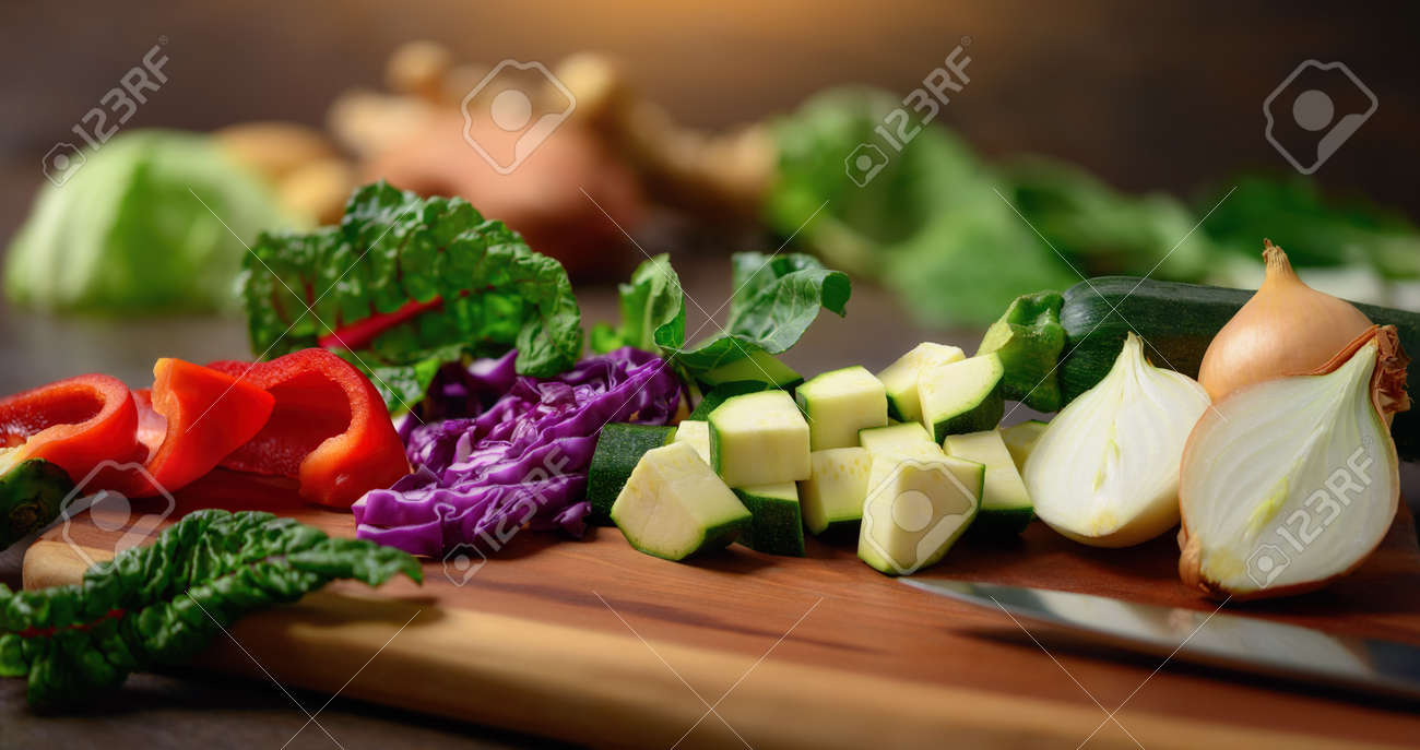 Cooking vegetables on a wooden cutting board. A closeup with shallow focus showing colorful, nutritious and delicious food ingredients as a healthy lifestyle concept. - 148545785