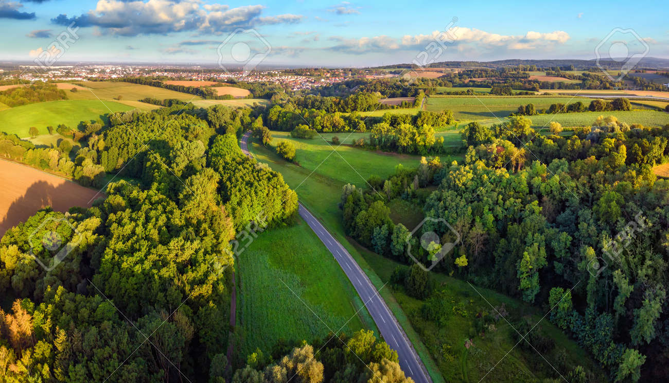 Idyllic German landscape shot from above in early morning sunlight: meadows and forests with blue sky and a road leading to a small town on the horizon - 149775554