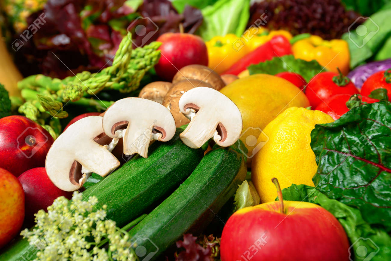 Colorful appetizing fruits and vegetables, a delicious looking closeup studio shot motivating for self-care and leading a healthy lifestyle, with cut mushrooms in focus - 148183198