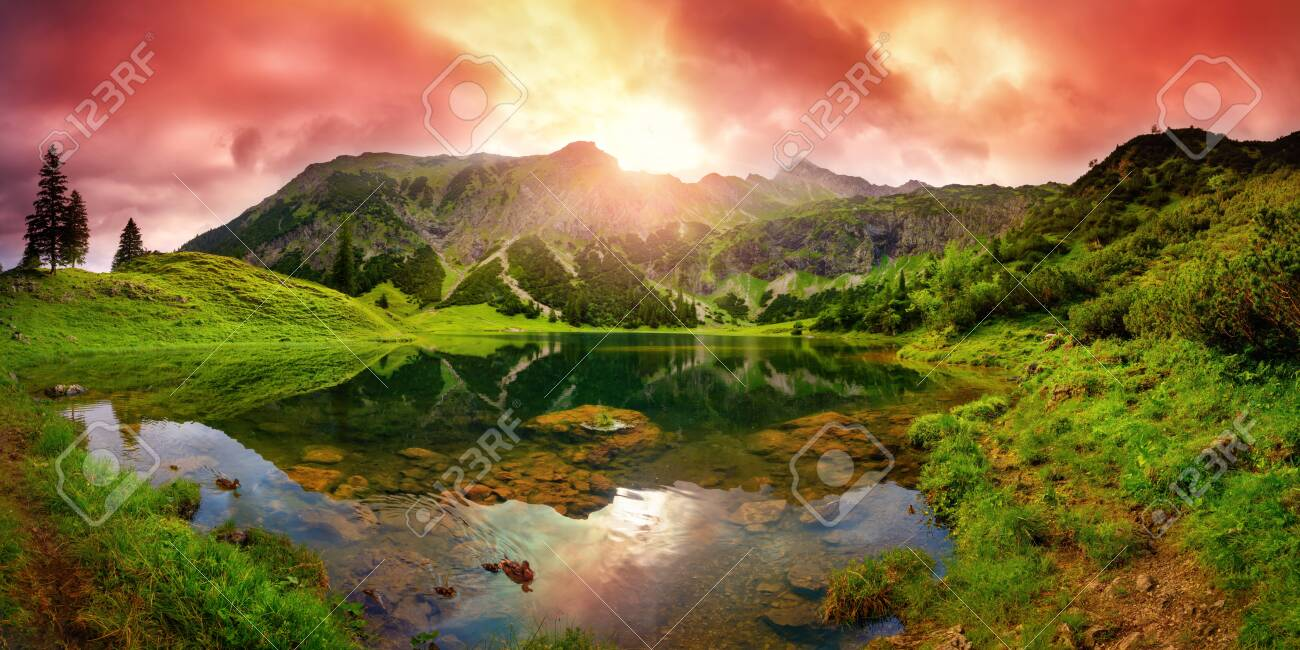 Dramatic sunrise at a lake in the Alps with mountains, red clouds reflected in the clear water and paths leading through the vibrant green grass - 151615450