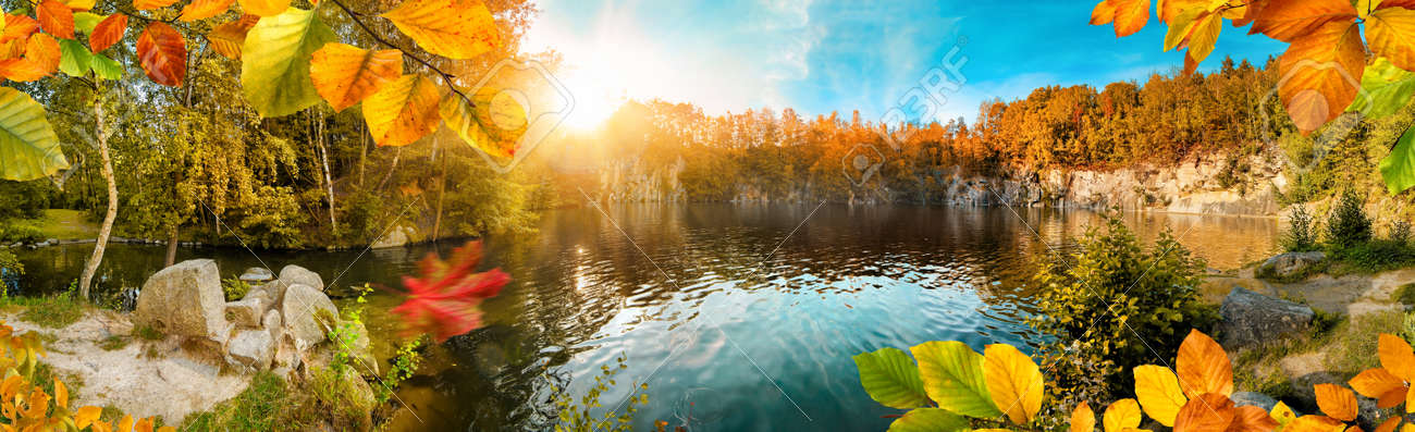 Magnificent autumn landscape panorama with colorful foliage framing a beautiful blue lake, with sun and blue sky - 156640003