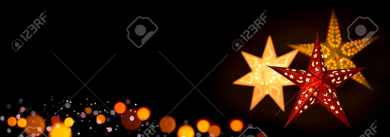 Shining red and gold Christmas star lanterns framing a simple, extra wide black background as copy space - 159388402