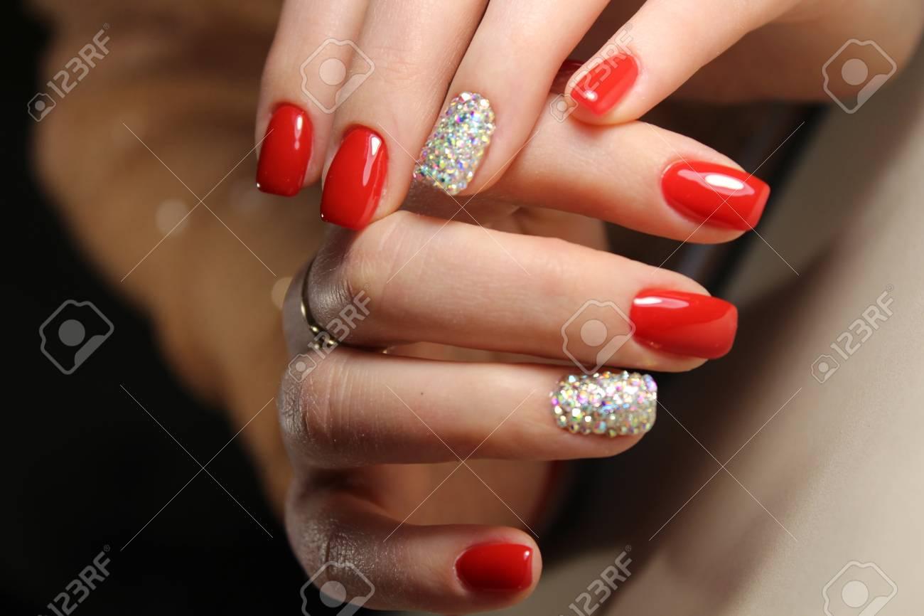 Las Uñas De Diseño De Manicura Son De Color Rojo Brillante Y Diamantes De Imitación