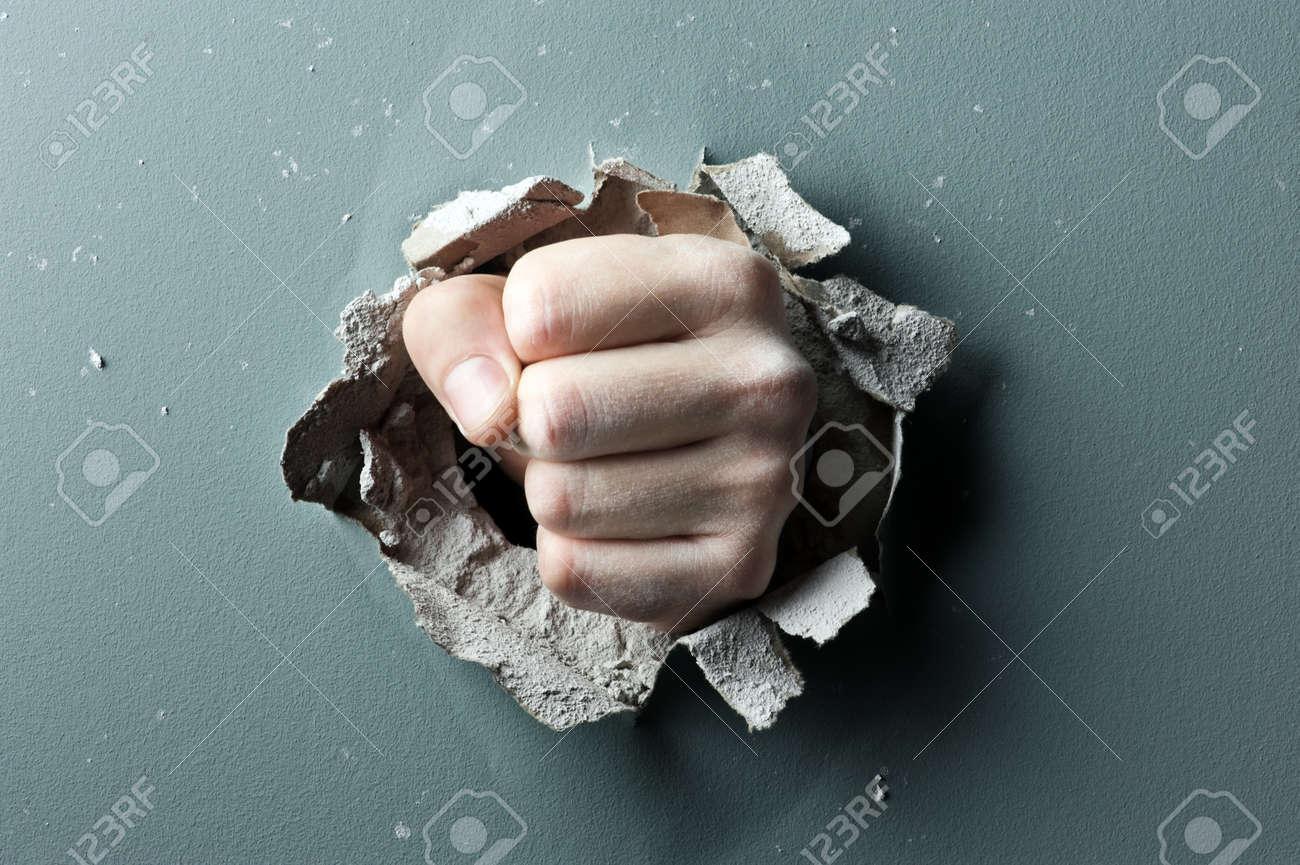 a wall is broken through by a fist Standard-Bild - 18022893