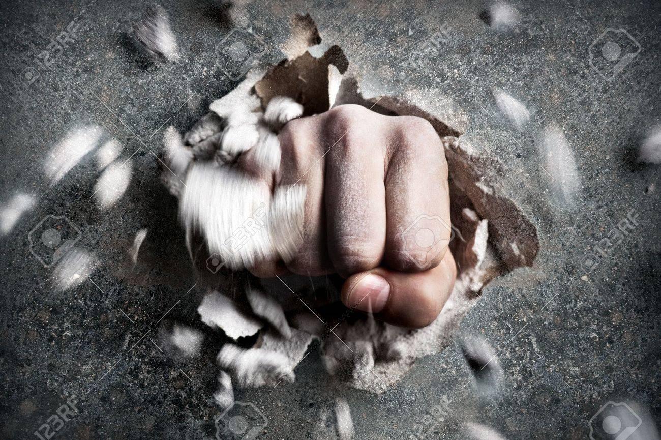 a wall is broken through by a fist Standard-Bild - 20301909