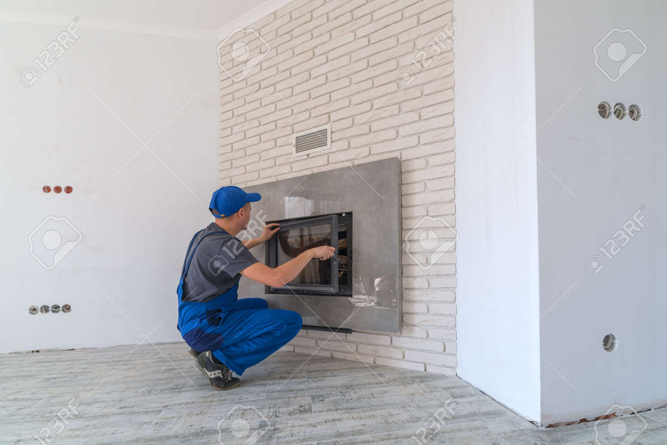 Fireplace installing in white brick wall - 48798463
