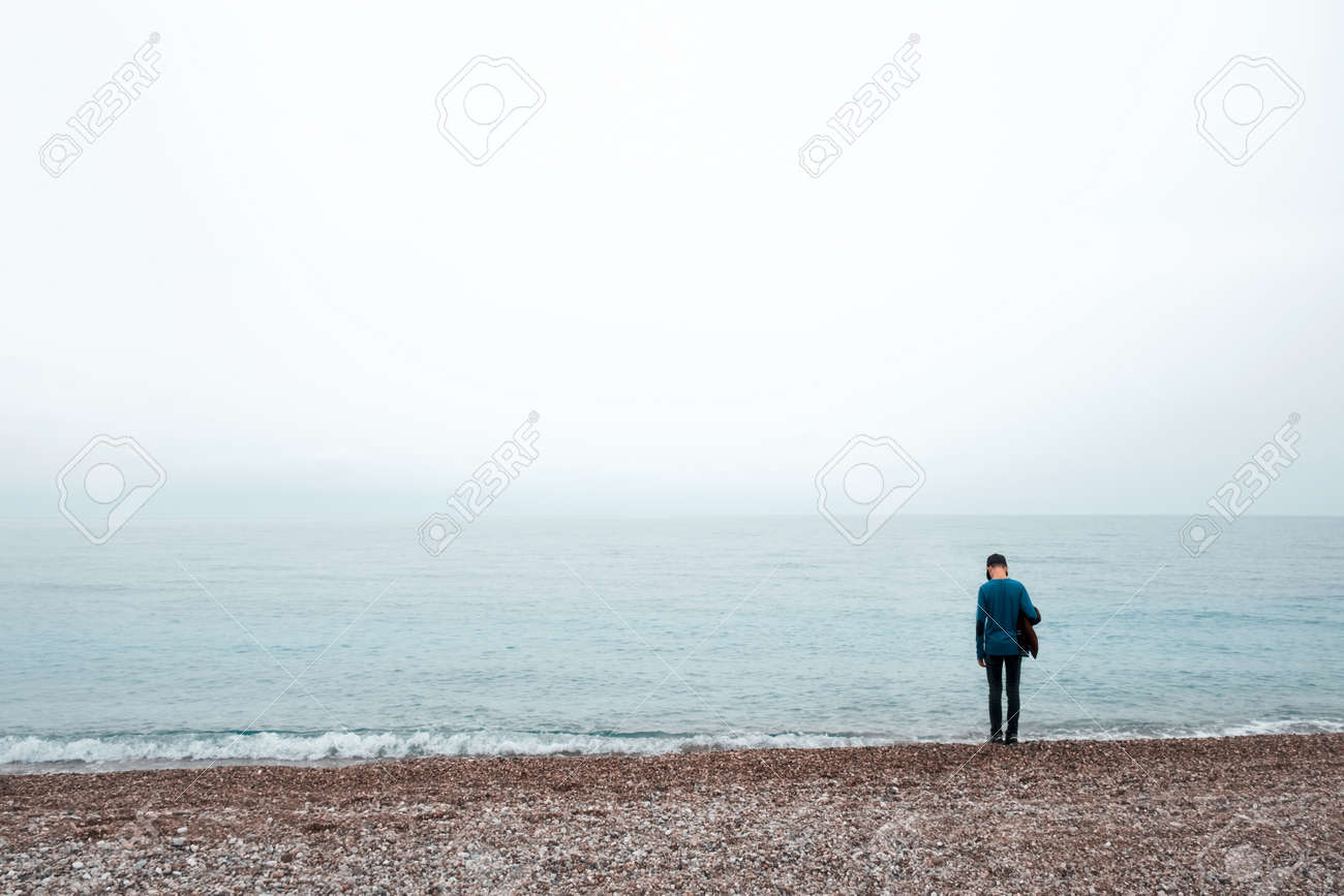 Alone boy stay near sea cloudy sky and foggy water stock photo 78595827