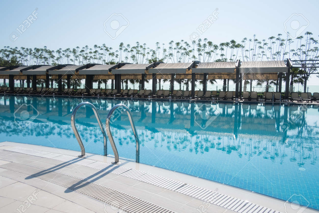 Swimming pool with sunshades and lounge chair in morning time...