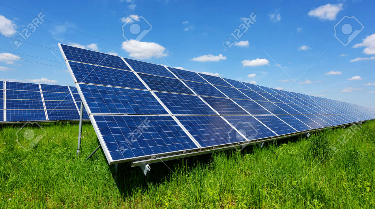 Solar panel on blue sky background. Green grass and cloudy sky. Alternative energy concept - 92057664