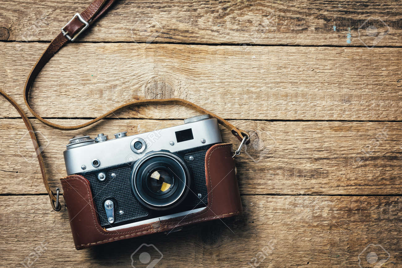 Grunge Camera Vector : Old vintage film photo camera with brown leather strap on grunge