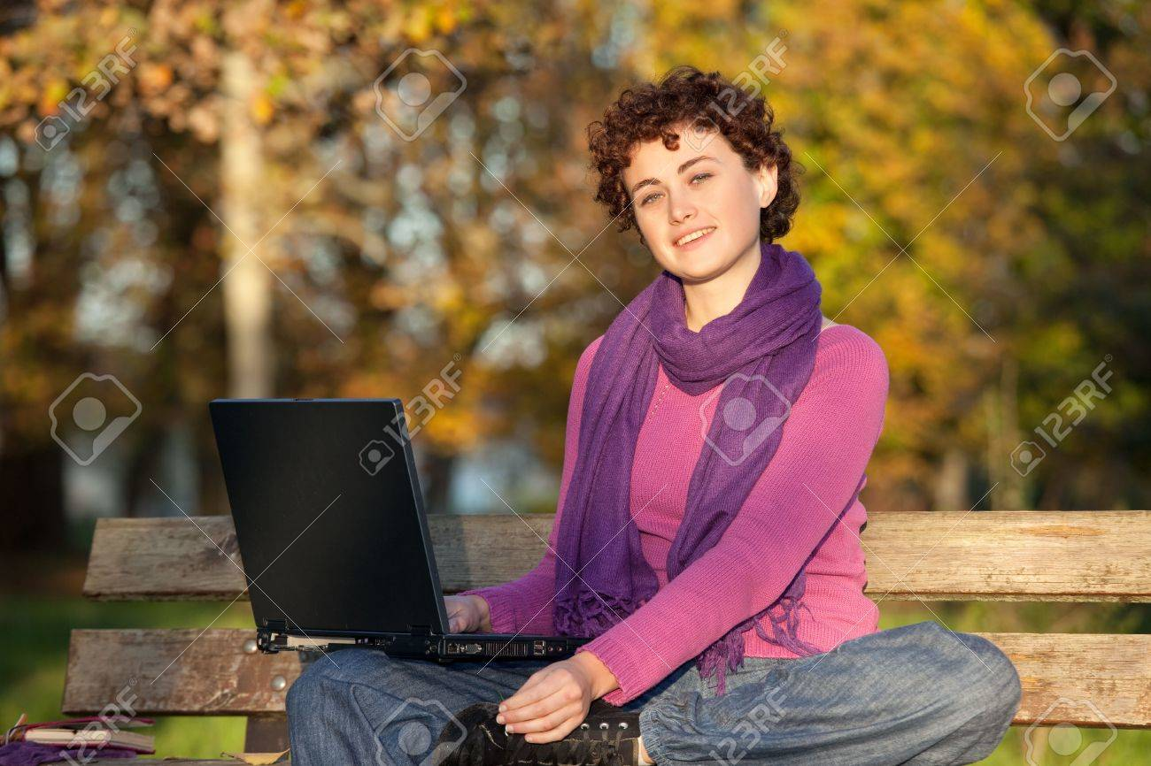 Young woman sitting on park bench smiling with laptop. Stock Photo - 9466976