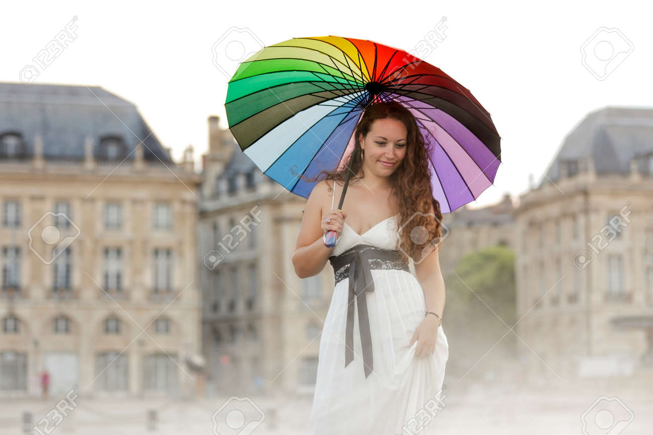 woman posing with colorful umbrella on traditional architecture in misty atmosphere , Bordeaux, france Stock Photo - 7292209