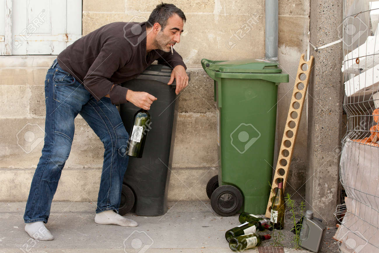 drunk man smoking cigarette and standing near trashcan Stock Photo - 7713118