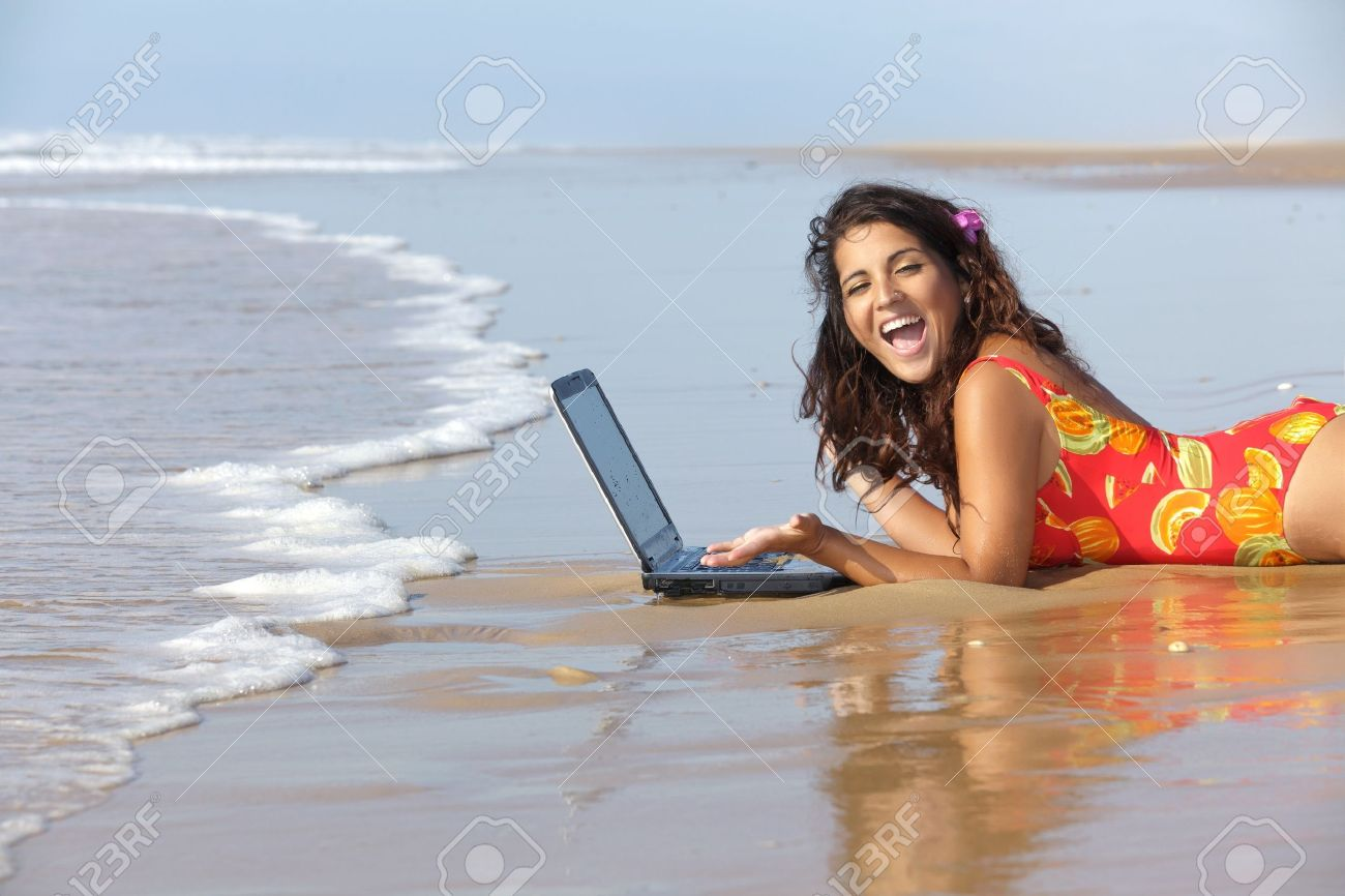 young woman using laptop on wet sand at beach Stock Photo - 10682317